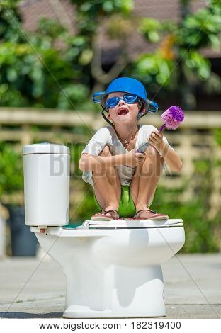 Absurd Picture: Cute Boy In Goggles Sitting On The Toilet, Which Is Installed In The Middle Of The S