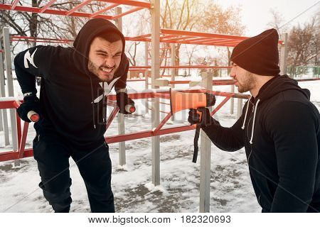 Fitness coach motivating via loudspeaker while male sporty adult doing triceps dips exercise. Winter workout.