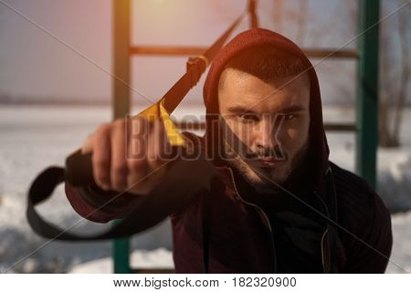 Young caucasian or middle eastern man doing exercise with fitness straps outdoors. Male adult in sportswear working out. Winter workout
