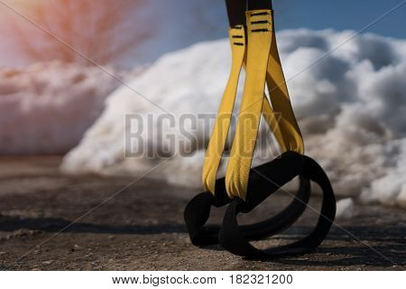 Fitness straps on background of snow. Winter workout. Healthy lifestyle.