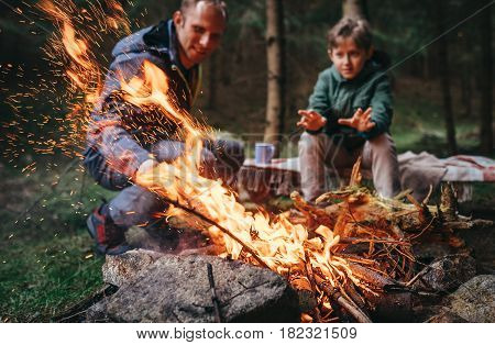 Father and son warms near campfire in forest