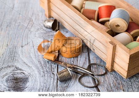 Wooden box with spools of thread, measuring tape, old scissors and thimbles on a wooden table.