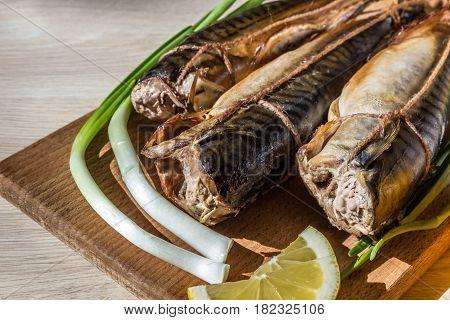 Smoked mackerel (raw fish) on wooden hardboard on wooden table