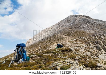 Backpacks on highland mountain trail with rocky peak ahead on cloudy day