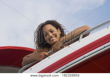 Mixed race woman leaning over edge of boat