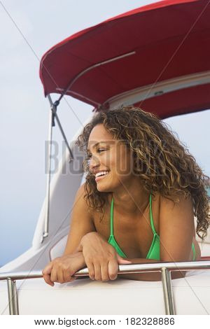 Mixed race woman laying on boat