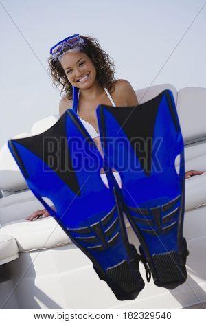 Mixed race woman in snorkel gear on boat