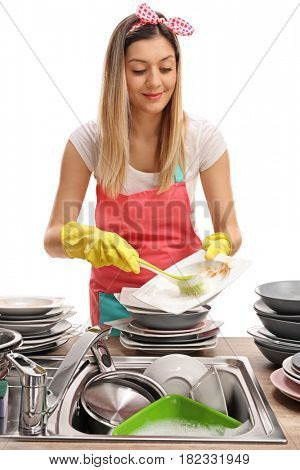 Young woman doing the dishes with a brush isolated on white background