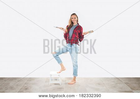 Beautiful young woman in working clothes holding paintbrushes, smiling happily, ready for home renovation.