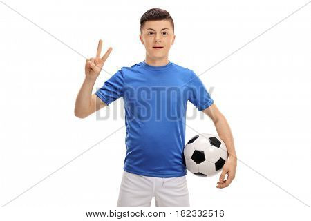Teenage soccer player with a football making a victory sign isolated on white background