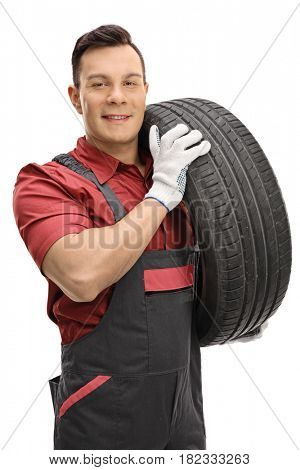 Young mechanic carrying a tire and looking at the camera isolated on white background
