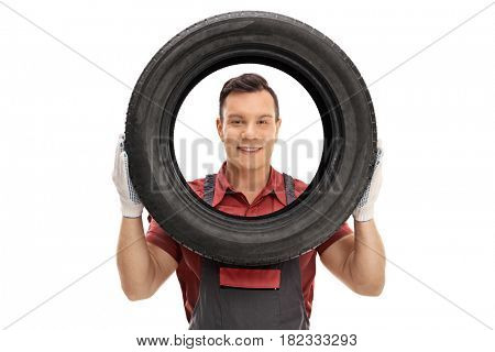 Mechanic looking at the camera through a tire isolated on white background