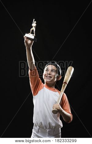Mixed race boy holding baseball trophy and baseball bat