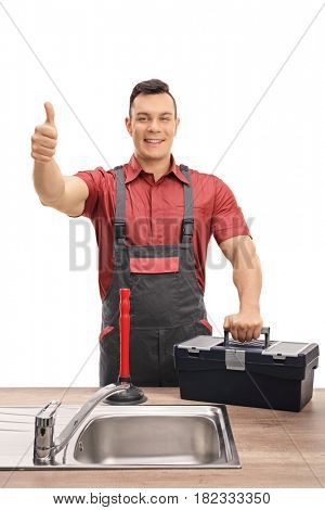 Plumber with a toolbox and a plunger making a thumb up sign behind a sink isolated on white background