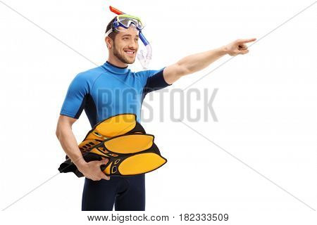 Man in a wetsuit with snorkeling equipment pointing in the distance isolated on white background