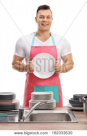 Young man in an apron showing a clean plate isolated on white background