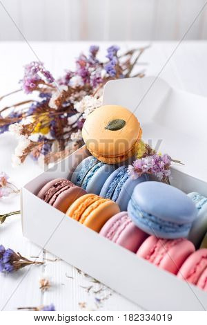 White box with macarons of various colours and flowers. Various colour macarons.