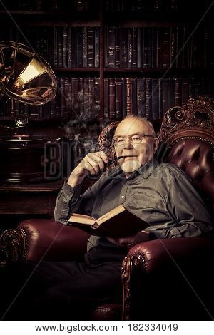 An old intelligent man listens to an old gramophone in his library. Retirement.