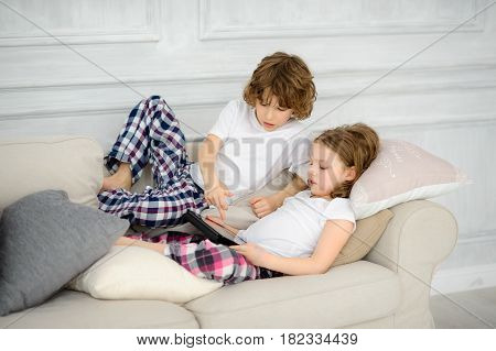Two children the boy and the girl lie on a sofa with the tablet in hands. They with interest look at the screen. Hobby of modern children.