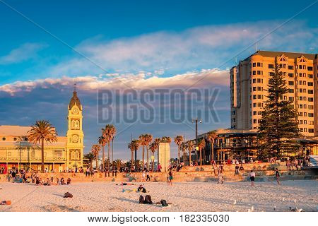 Adelaide Australia - August 29 2016: People meeting sunset at Glenelg Beach on a warm evening. Viewed towards Moseley Square and Pioneer memorial.