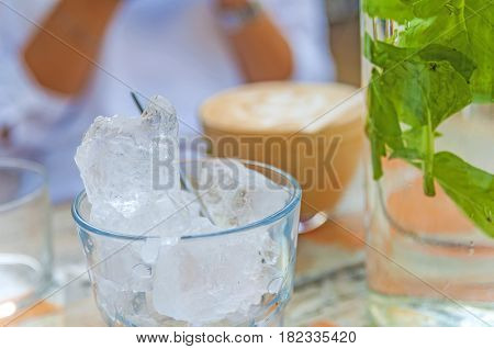Glasses with ice cubes on wooden table in cafe