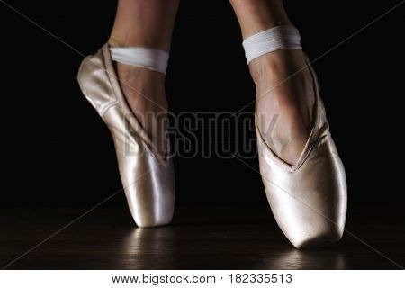 Close-up classic ballerina's legs in pointes on the black wooden dark floor