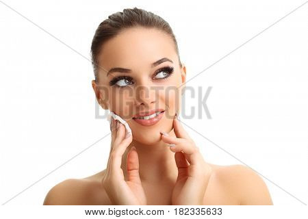 Adult woman smiling at camera and using cotton pad against white isolated background
