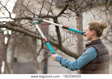 Young woman taking care of garden. Cutting tree branch.