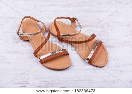 Pair of women's sandals on a white wooden background.