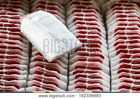 Closeup tea bags with red labels arranged in box