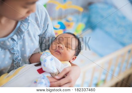 Sister takecare asian new born baby to sleep in thr cradle