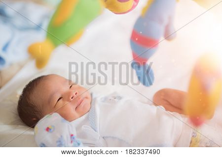 Baby sleep in cot with over head fish mobile