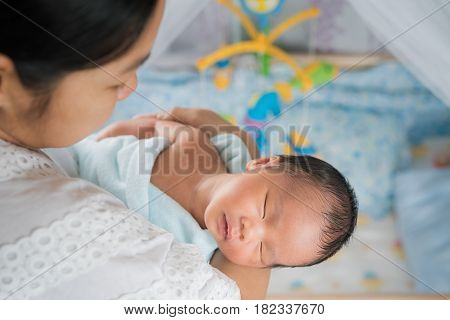 Mother takecare asian new born baby to sleep in thr cradle