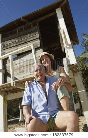 Hispanic couple sitting near lifeguard tower