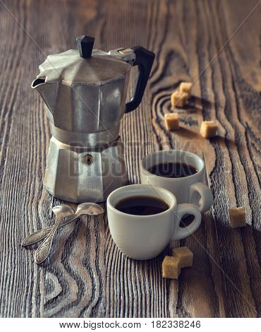 Two cups of coffee with pieces of cane sugar and Italian  coffee maker on wooden table.  Toned image.