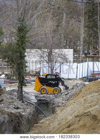 day view of mini yellow excavator with shovel in action at construction site