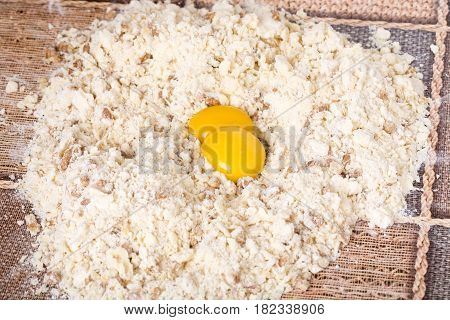 Making dough with walnuts and egg yolks on a table as a background.