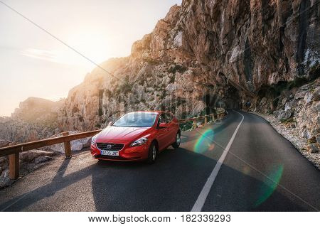 Alcudia, Mallorca, Spain - May 24, 2016: Red car Volvo V40 traveling on the mountain serpentine through a tunnel of a rock along the coast against the sunshine with lens flare. Roadtrip around Spain
