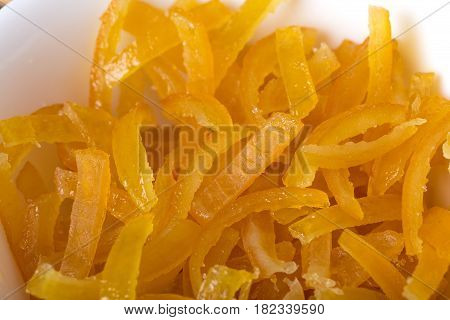 Candied orange peels closeup in white bowl. Macro. Photo can be used as a whole background.
