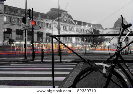Toulouse, France - October 27, 2016; Cycle leaning against railing under morning mist in city with glow of lights on street path and buildings with Matabiau Railway Station in background Toulouse France.