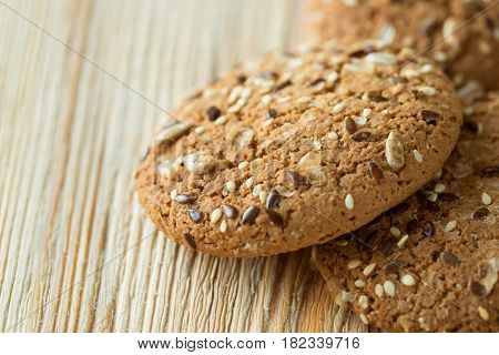 Few oatmeal cookies with seeds on a wooden table.