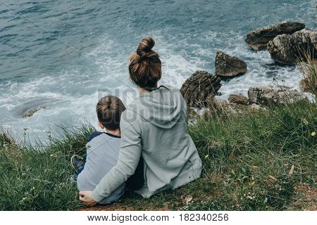 Hipster Mother And Her Son Watching A Crashing Waves At Sea, Montenegro
