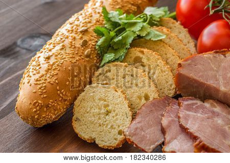 Sliced baguette with ham tomatoes and parsley on a wooden table