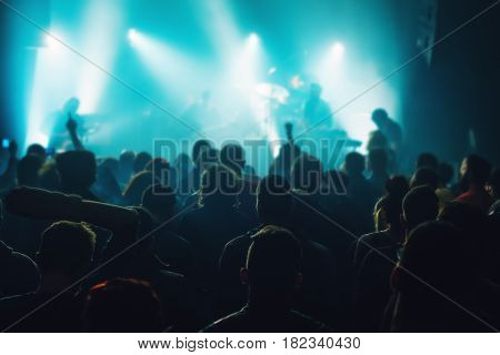 Music concert crowd people at popular live rock performance fans hands in the air selective focus