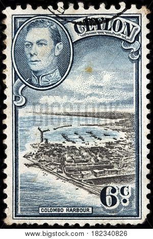LUGA RUSSIA - FEBRUARY 7 2017: A stamp printed by CEYLON shows image portrait of King George VI against beautiful view of Colombo harbor. Colombo is largest city of Sri Lanka circa 1938.