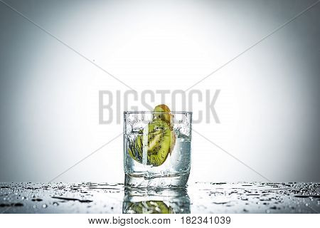 The water splash in glass with kiwi fruits of gray studio color