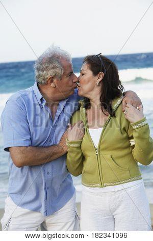 Hispanic couple kissing on beach