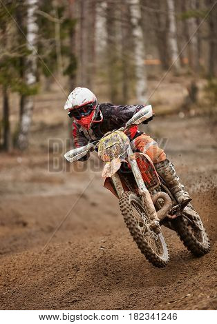 Motocross enduro driver in action accelerating the motorbike on the race track.