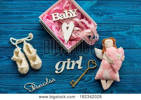 Wooden inscriptions, key, pink angel, ribbon lace and baby booties on a blue wooden background. Top view. Collage