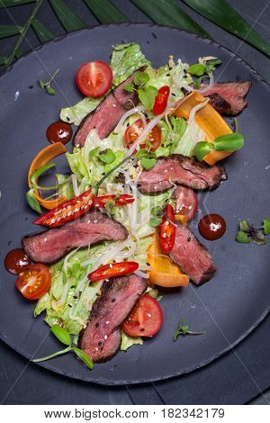 Japanese salad with meat, chili pepper, cherry tomatoes and fresh sprouts